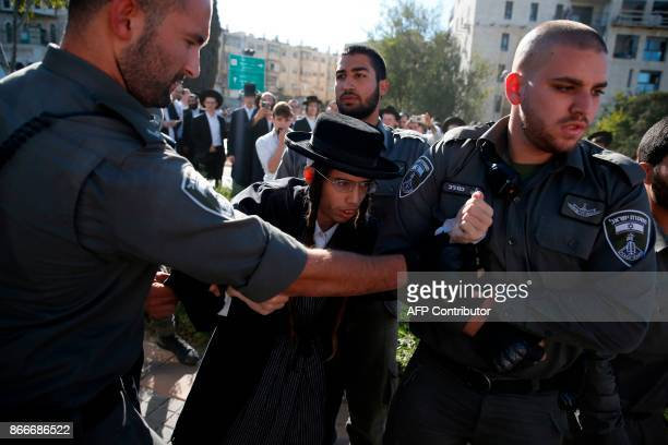 TOPSHOT Members of the Israeli security forces detain an ultraOrthodox Jew during a demonstration against Israeli army conscription in Jerusalem on...