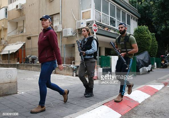 Members of the Israeli security forces patrol the area following an attack by an unidentified gunman who opened fire at a pub in Tel Aviv killing two...