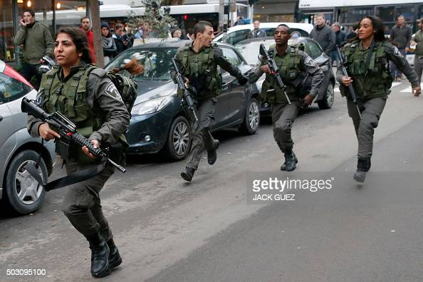 Members of the Israeli security forces search the area following an attack by an unidentified gunman who opened fire at a pub in the Israeli city of...