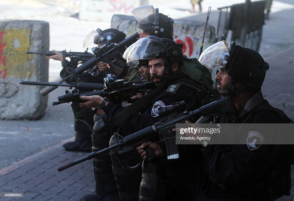 Members of the Israeli security forces stand guard after Palestinian protestors set barricades on fire and block roads following a protest to show support for resistance movement Hamas in Hebron, West Bank on August 22, 2014.