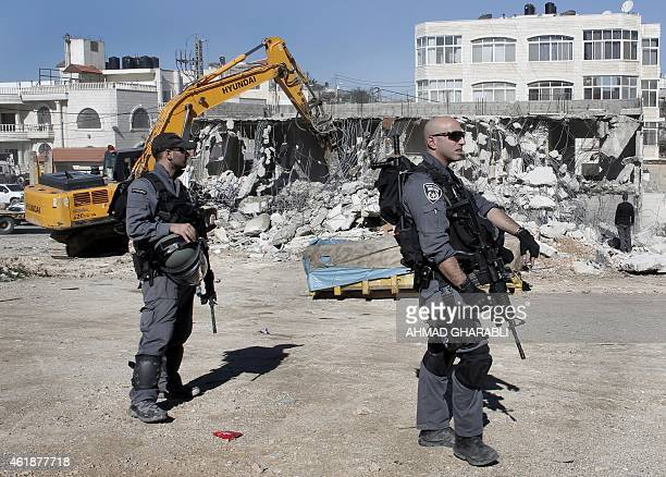 Members of the Israeli security forces stand guard as bulldozers hired by the Jerusalem municipality destroy a Palestinian house in the Israeli...