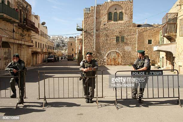 Members of the Israeli security forces stand guard they evacuate Jewish settlers from two homes in the heart of the West Bank city of Hebron on...