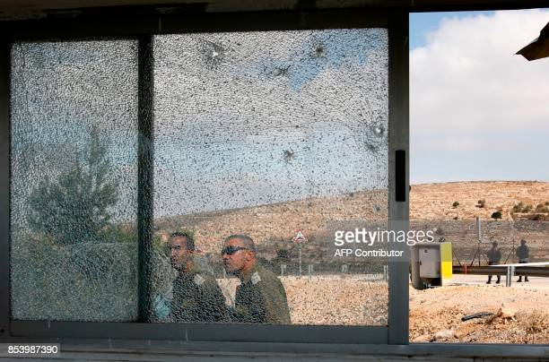 TOPSHOT Members of the Israeli security forces walk past the shattered glass of the security post at the entrance to the West Bank settlement of Har...