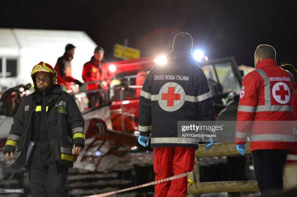 Members of the Italian Alpine rescue team and fireman take part in the rescue of six Russian tourists who died after an accident in Mount Cermis, near Cavalese in Val di Fiemme, on January 5, 2013. A snowmobile accident in the Italian Alps left six tourists dead and two others seriously injured. The eight -- all from eastern Europe, or Russia -- were riding on the vehicle across an unlit slope on Mount Cermis in the Trento region, rescuers said. Mount Cermis was the scene of two deadly cable car accidents in 1976 and 1998. In the latter a US military plane cut a cable supporting a gondola of an aerial tramway. AFP PHOTO / GIUSEPPE CACACE / AFP PHOTO / Giuseppe CACACE