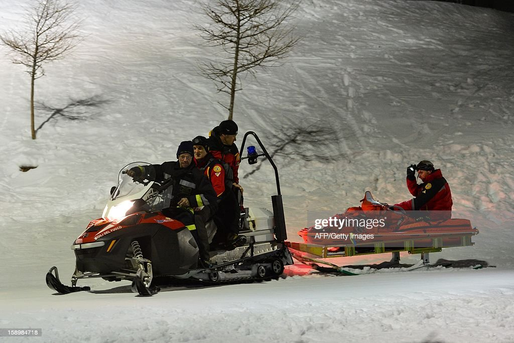 Members of the Italian Alpine rescue team and fireman take part in the rescue of six Russian tourists who died after an accident in Mount Cermis, near Cavalese in Val di Fiemme, on January 5, 2013. A snowmobile accident in the Italian Alps left six tourists dead and two others seriously injured. The eight -- all from eastern Europe, or Russia -- were riding on the vehicle across an unlit slope on Mount Cermis in the Trento region, rescuers said. Mount Cermis was the scene of two deadly cable car accidents in 1976 and 1998. In the latter a US military plane cut a cable supporting a gondola of an aerial tramway. AFP PHOTO / GIUSEPPE CACACE