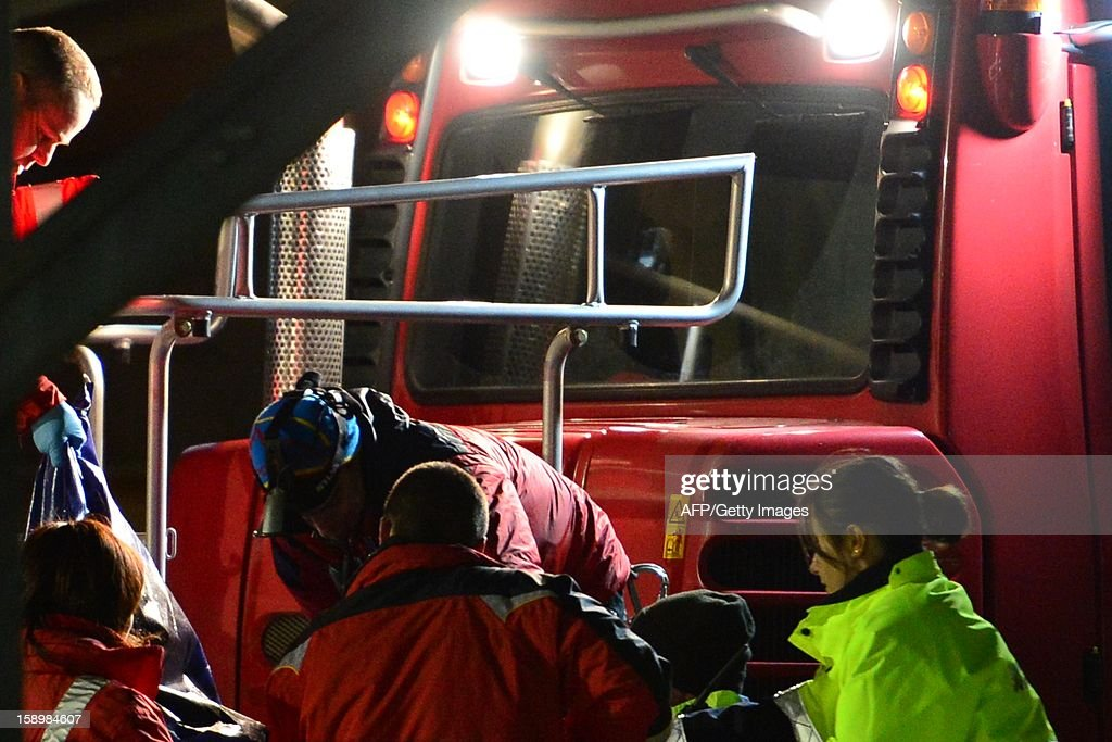 Members of the Italian Alpine rescue team carry the body of one of six Russian tourists who died after an accident in Mount Cermis, near Cavalese in Val di Fiemme, on January 5, 2013. A snowmobile accident in the Italian Alps left six tourists dead and two others seriously injured. The eight -- all from eastern Europe, or Russia -- were riding on the vehicle across an unlit slope on Mount Cermis in the Trento region, rescuers said. Mount Cermis was the scene of two deadly cable car accidents in 1976 and 1998. In the latter a US military plane cut a cable supporting a gondola of an aerial tramway. AFP PHOTO / GIUSEPPE CACACE