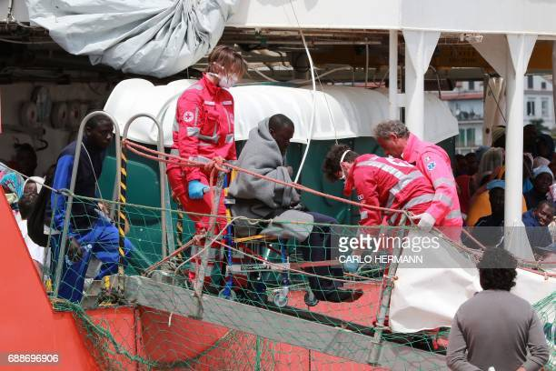 Members of the Italian Red Cross help a migrant to disembark from the Aquarius rescue Ship run by NGO SOS Mediterranee and Medecins Sans Frontieres...