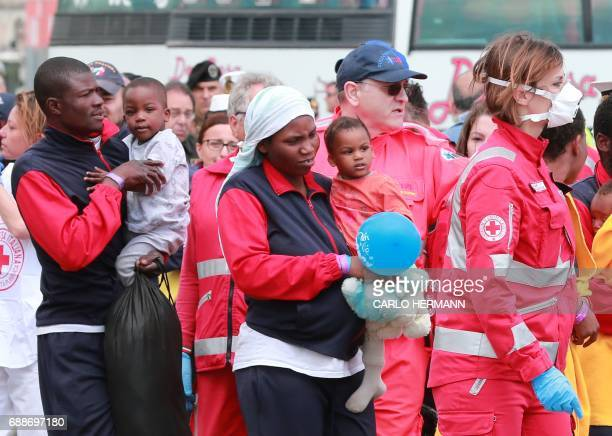 Members of the Italian Red Cross help migrants holding children to disembark from the Aquarius rescue Ship run by NGO SOS Mediterranee and Medecins...