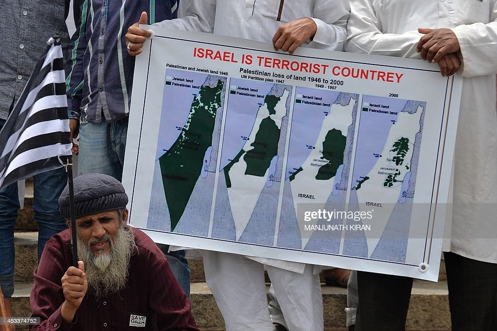 Members of the Jamiat Ulamia-I-Hind hold a poster while taking part in protest demonstration in Bangalore on August 9, 2014, as part of a protest organised in support of the Global Day of Rage against Israel's actions in Gaza. The demonstrators urged the UN to convene a special general assembly to condemn the Israeli aggression and demand the country to abide by the International laws, Agreements and Conventions. AFP PHOTO/Manjunath KIRAN
