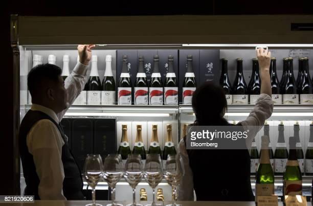 Members of the Japan Awasake Association display bottles of sparkling sake during a Sake Marche event at the Isetan Shinjuku department store...