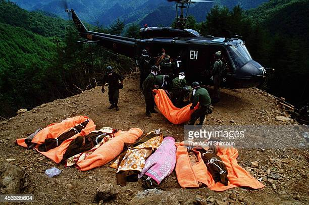 Members of the Japan Ground SelfDefense Force carry bodies by a helicopter at the ridge of Mount Osutaka on August 14 1985 in Ueno Gunma Japan Japan...