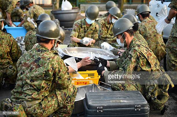 Members of the Japan SelfDefense Forces make rice balls at the souprun operated at the evacuation center a day after the 2016 Kumamoto Earthquake at...