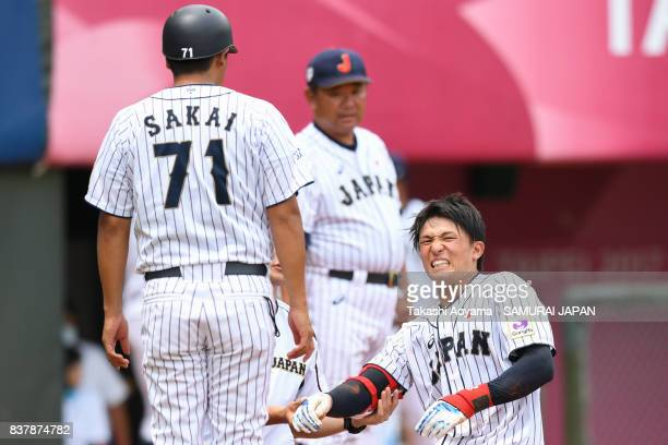 Members of the Japan team checks Takeshi Miyamoto after Miyamoto was hit by a pitch in the 5th inning during the Baseball Group B match between Japan...