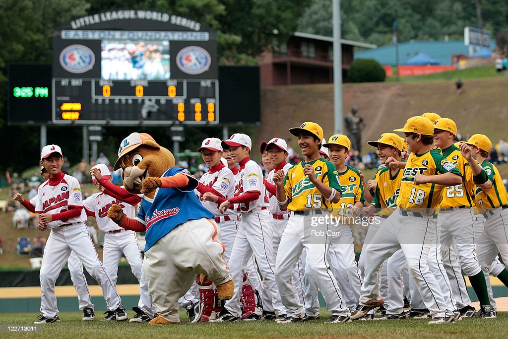 Members of the Japan team from Hamamatsu City, Japan (L) and members of the West team from Huntington Beach, California dance with mascot 'Dugout' before the start of the Little League World Series championship game on August 28, 2011 in South Williamsport, Pennsylvania. The West team defeated the team from Japan 2-1.