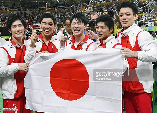 Members of the Japanese men's gymnastics team Ryohei Kato Kenzo Shirai Kohei Uchimura Koji Yamamuro and Yusuke Tanaka hold the national flag as they...