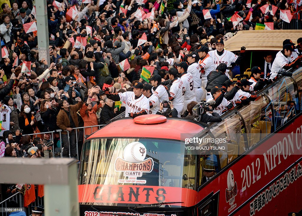 Members of the Japanese professional baseball team and victors of this year's Japan Series, the Tokyo Yomiuri Giants, wave to thousands of fans from open-top buses during a parade to celebrate their victory, in Tokyo's Ginza shopping district on November 25, 2012. The Giants beat the Hokkaido Nippon Ham Fighters in the final game on November 3 to take the best-of-seven series 4-2 for their 22nd Japan Series title. AFP PHOTO / Yoshikazu TSUNO