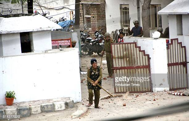 Members of the Jat community protest for reservations in government services as they throw stones at police personnel hiding behind main gate of...