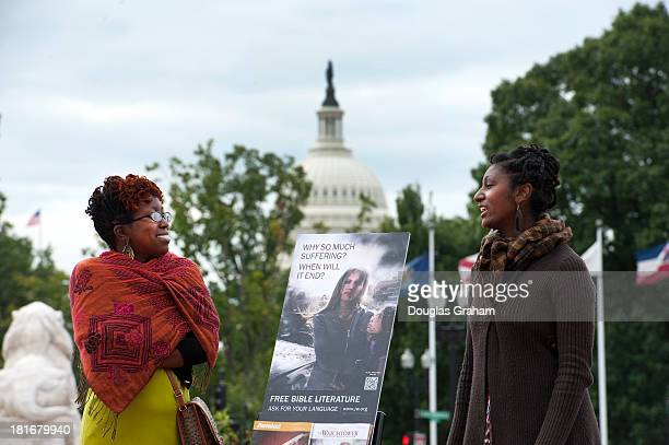 Members of the Jehovah's Witnesses church talk with a sign about suffering and free bible's in front of Union Station with the US Capitol dome as a...