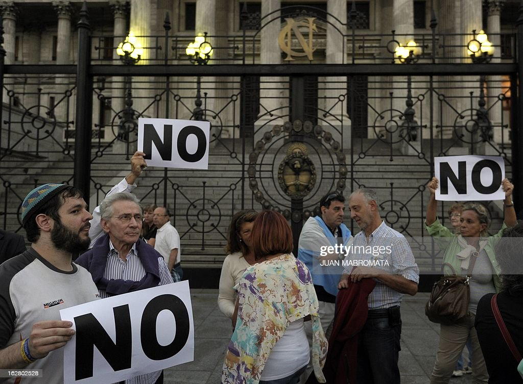 Members of the Jewish community hold signs outside the Congress building in Buenos Aires on February 27, 2013, while legislatives discuss the possibility of an agreement with Iran to establish a truth commission over a terrorist attack that took place in 1994. Eight Iranian nationals are still wanted in connection with the bombing of the Argentine Israelite Mutual Association (AMIA is Spanish), which left 85 dead and 300 wounded. AFP PHOTO / Juan Mabromata