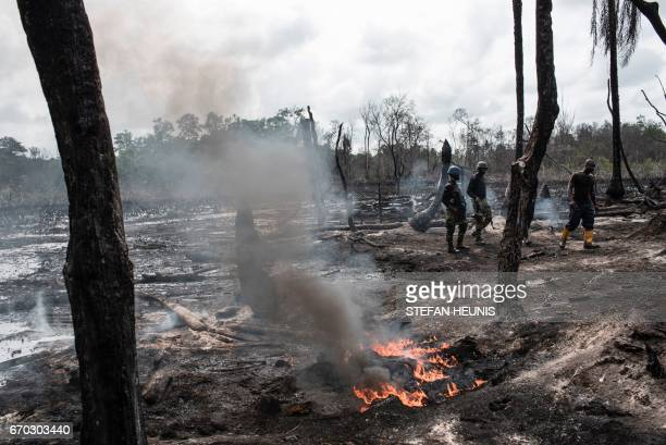 Members of the Joint Task Force Operation Delta Safe walk through a recently destroyed illegal oil refinery on April 19 2017 in the Niger Delta...