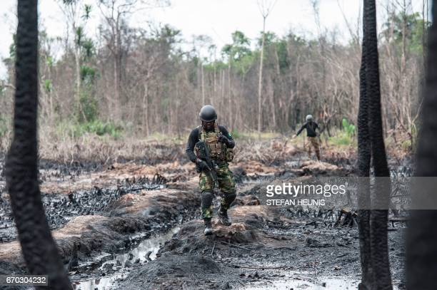 TOPSHOT Members of the Joint Task Force Operation Delta Safe walk through an abandoned site of an illegal oil refinery on April 19 2017 in the Niger...