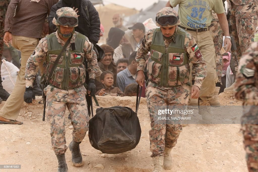 Members of the Jordanian military carry the bag of a Syrian refugee woman on the Jordanian side of the Hadalat border crossing, a military zone east of the capital Amman, as an influx of new refugees arriving from Syria enter the country on May 4, 2016. According to the Jordanian Commander of the Border Guards Brigadier Saber Al-Mahayreh, around 5000 Syrians fleeing from recent attacks on the northern Syrian city of Aleppo are trying to cross into Jordan in search of safety and most are exhausted and desperately in need of help and medical treatment. MAZRAAWI