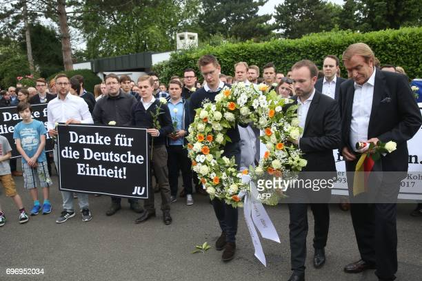 Members of the Jungen Union the youth organisation of the Christian Democratic Union hold a placard which reads 'Thanks you for the Unification of...
