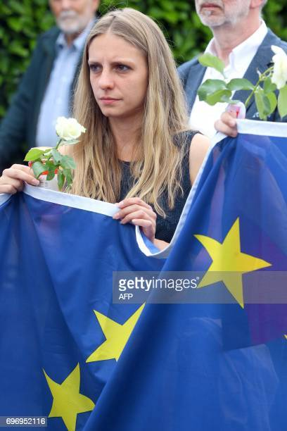 A members of the Jungen Union the youth organisation of the Christian Democratic Union holds a flower and the EU flag as they lay a wreath in front...