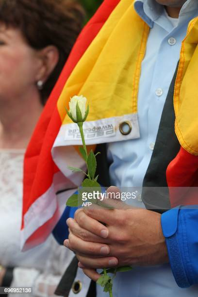 A members of the Jungen Union the youth organisation of the Christian Democratic Union holds a flower and the German flag as they lay a wreath in...
