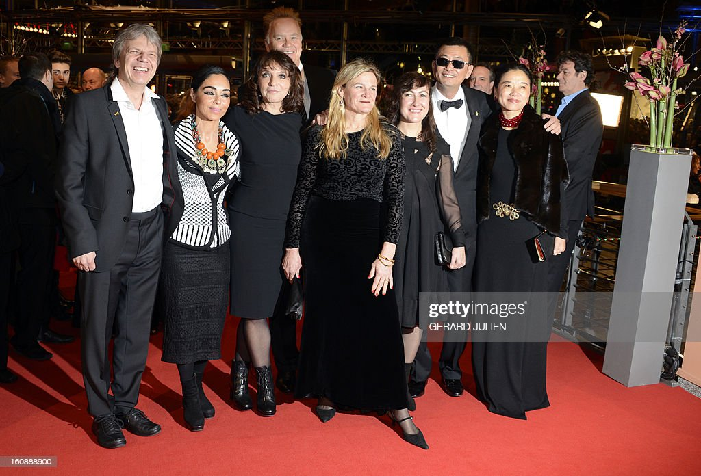 Members of the jury, German director and screenwriter Andreas Dresen, Iranian director Shirin Neshat, Danish director Susanne Bier, US actor and director Tim Robbins, US cinematographer Ellen Kuras, Greek director Athina Rachel Tsangari, Jury president Hong Kong Chinese director Wong Kar-Wai and his wife Esther pose on the red carpet of the opening film of the Berlinale film festival , 'Yi dai zong shi' (The Grandmaster) in Berlin, on February 7, 2013. The 63rd Berlin film festival opens with a gala screening of Chinese director Wong Kar Wai's martial arts epic about the mentor of kung fu superstar Bruce Lee. AFP PHOTO / GERARD JULIEN
