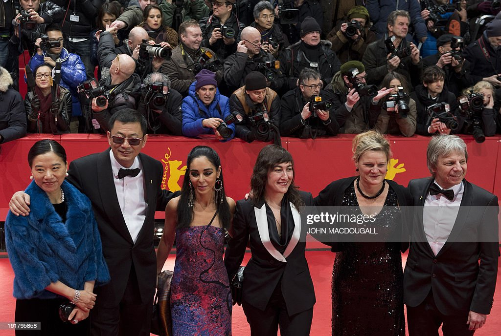 Members of the jury, (from R to L) German director Andreas Dresen, US cinematographer Ellen Kuras, Greek director Athina Rachel Tsangari, Iranian director Shirin Neshat, Jury president Hong Kong Chinese director Wong Kar-Wai and his wife pose for photographers as they arrive on the red carpet for the awards ceremony of the 63rd Berlinale Film Festival, in Berlin on February 16, 2013.
