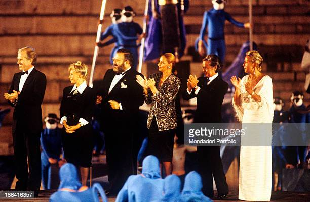 Members of the jury of honor are applauding on the stage of the Arena di Verona at the end of Aida passage the Roman arena hosts a show with many...