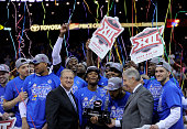 Members of the Kansas Jayhawks celebrate with the Big 12 Basketball Tournament trophy as they celebrates the win over West Virginia Mountaineers 8171...