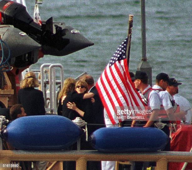Members of the Kennedy and Bessette families embrace at the stern of the Coast Guard ship Sanibel as they prepare to travel to the USS Briscoe 22...
