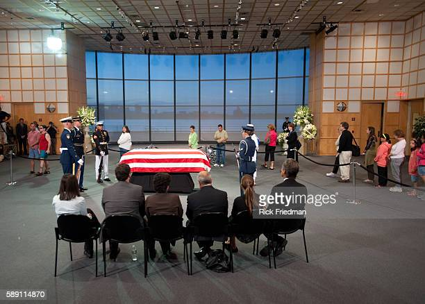 Members of the Kennedy family sit near the casket containing the body of Senator Edward M Kennedy as people pass by to pay their respects at the John...