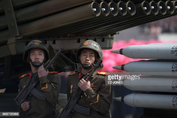 Members of the Korean People's Army ride on mobile missile launchers during a military parade marking the 105th anniversary of the birth of late...