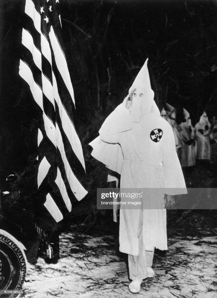 Members of the Ku Klux Klan saluting the american flag, Photograph, America, October 18th 1937 (Photo by Imagno/Getty Images) [Mitglieder des Ku Klux Klan marschieren salutierend an der ameikanischen Flagge vorbei, Photographie, 18, Oktober 1937]