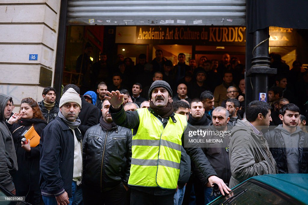 Members of the kurdish community attend on January 10, 2013 in front the Kurdish Culture Institute in Paris, in the district where a co-founder of the Kurdistan Workers' Party (PKK) and two other activists were found shot dead, a day after it emerged that Turkey and the jailed leader of the banned group were holding peace talks. The bodies of the women were found in the early hours with gunshot wounds to the head and neck, inside the building in the 10th arrondissement of the French capital. Hundreds of Kurds gathered in front of the centre to protest at the deaths, with some chanting 'We are all PKK!' and 'Turkey assassin, Hollande complicit', referring to French President Francois Hollande.