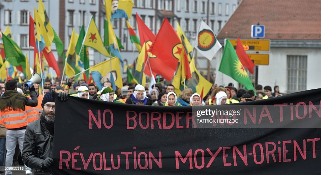 Members of the Kurdish community hold flags bearing a portait of jailed leader of Turkey's Kurd rebels, Abdullah Ocalan, in Strasbourg, eastern France, on February 13, 2016, during the annual rally of Kurds from all over Europe to denounce the detention of Abdullah Ocalan. take part in the annual rally of Kurds from all over Europe to denounce the detention of jailed leader of Turkey's Kurd rebels, Abdullah Ocalan, on February 13, 2016, in Strasbourg, eastern France, Ocalan was captured by Turkish undercover agents in Kenya in 1999, brought back to Turkey and sentenced to death. His sentence was later commuted to life. / AFP / PATRICK HERTZOG