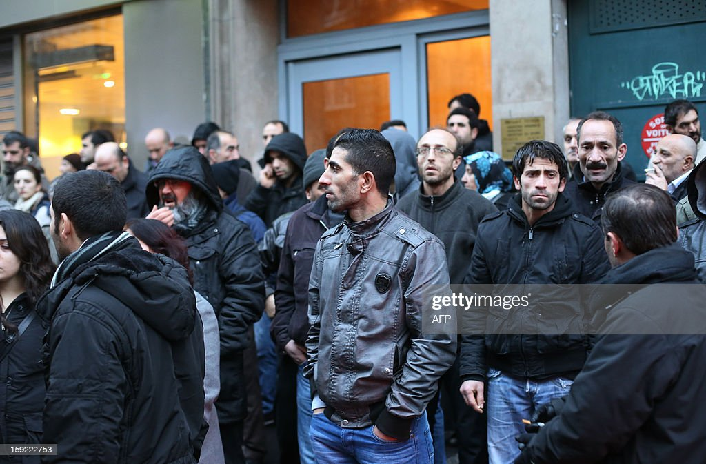 Members of the Kurdish community in France stand near the Kurdistan Information Bureau in Paris on January 10, 2013, where three Kurdish women were found killed with a gunshot to the head. The bodies of the women were found shortly before 2:00 am (0100 GMT) inside the building in the 10th arrondissement of the French capital. One of the women was 32-year-old Fidan Dogan who worked in the institute's information centre, according to its director, Leon Edart. The identities of the other two women, who were reportedly Kurdish activists but did not work at the Institute, were not immediately available. AFP PHOTO / THOMAS SAMSON