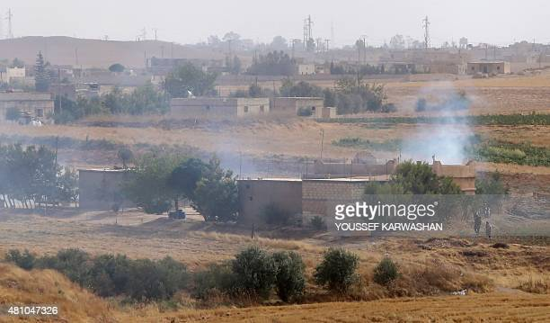 Members of the Kurdish People's Protection Units take position in a field in the village of Maarouf in the northeastern Syrian province of Hasakeh on...