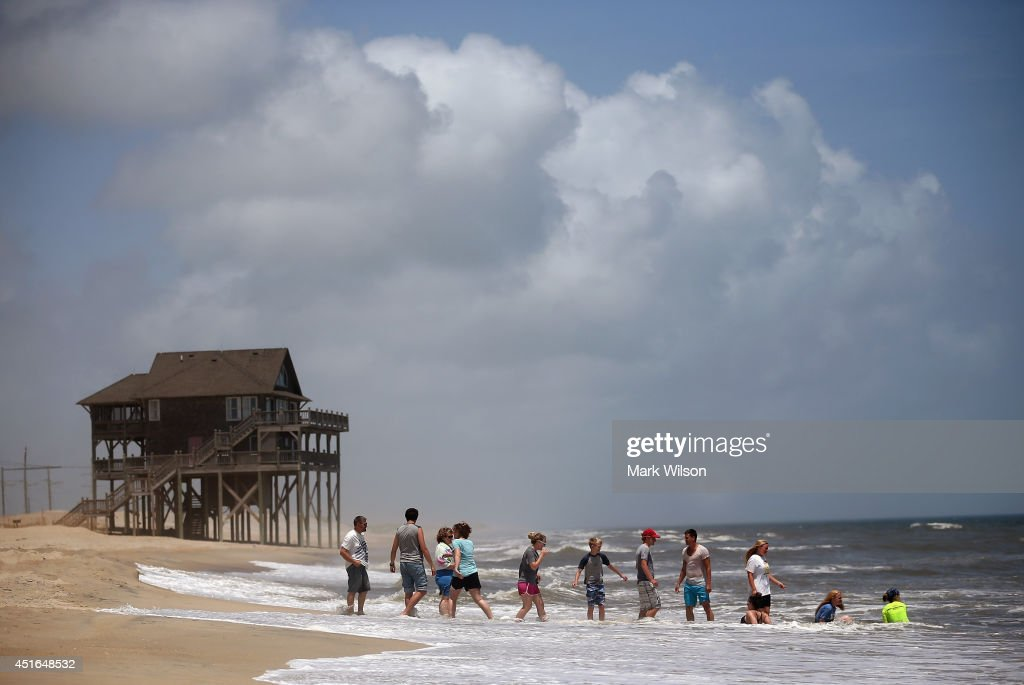Members of the large Garrison family from Kansas City, MO., play in the surf before complying with the mandatory evacuation orders for Hatteras Island, July 3, 2014 in Rodanthe, North Carolina. A Hurricane warning has been issued for North Carolina's Outer Banks due to approaching Hurricane Arthur that has been upgraded to a category 2 hurricane.
