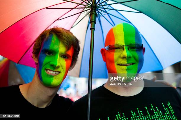 Members of the Lesbian Gay Bisexual and Transgender shelter from the rain as they take part in the annual Pride Parade in London on June 28 2014 AFP...