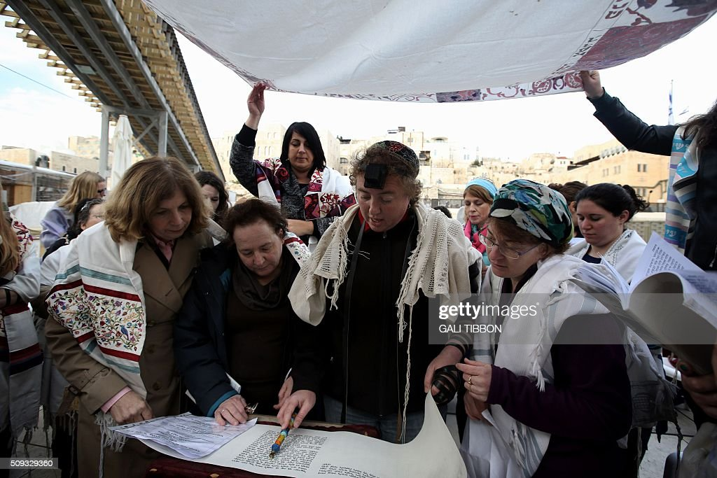 Members of the liberal religious group 'Women of the Wall' wear phylacteries and 'Tallit' shawls, traditional Jewish prayer apparel for men, as they pray at the Western Wall in Jerusalems Old City on February 10, 2016 marking Rosh Hodesh Adar (the first day of the Jewish month). / AFP / GALI TIBBON