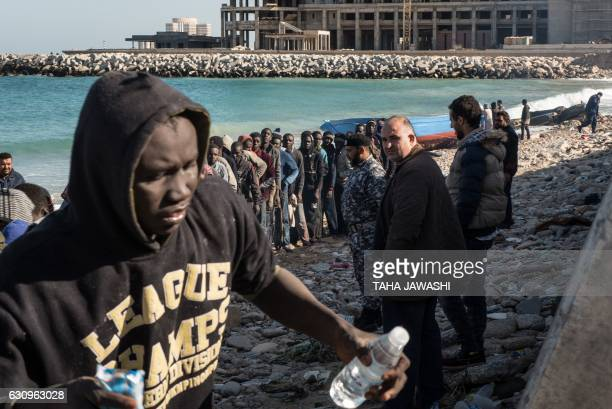 TOPSHOT Members of the Libyan Red Crescent and policemen inspect illegal immigrants who were aboard a boat that arrived to the shore of the Andalus...