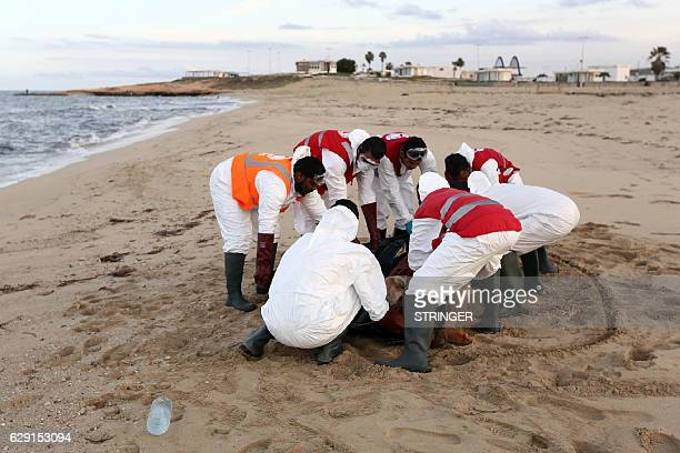 Members of the Libyan Red Crescent treat the drowned body of an illegal immigrant which washed ashore after a ship sank off Tajoura on the eastern...
