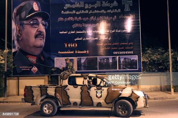 Members of the Libyan Special Forces loyal to the country's east strongman Khalifa Haftar ride in a pickup truck past a local advertisement billboard...