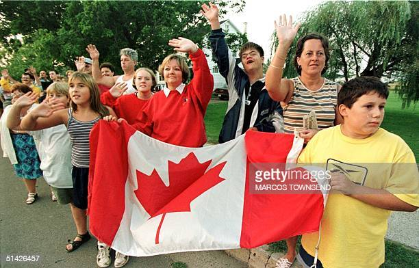 Members of the local Acadian population from Bouctouche New Brunswick hold a Canadian flag as they await the arrival of leaders during the 8th annual...