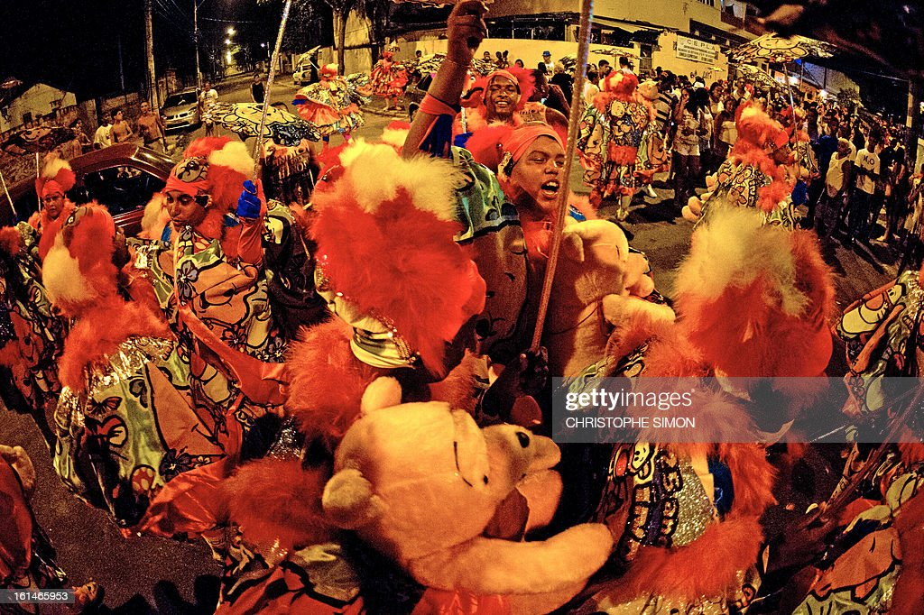 Members of the local 'Indio' carnival group of the Guadalupe neighborhood in northern Rio de Janeiro, Brazil, dance durintg their 'Bate Bola' traditional parade on February 10, 2013. AFP PHOTO/Christophe Simon