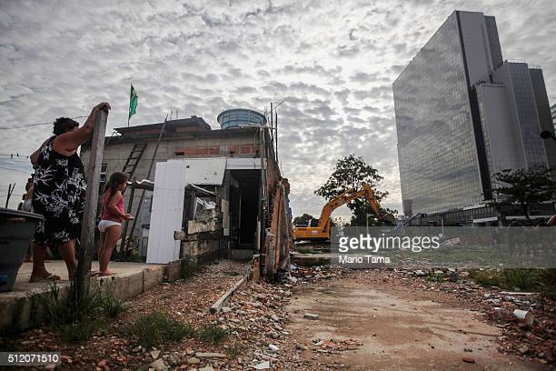 Members of the Lopes family watch from their remaining home during the demolition of the neighboring residents association building in the mostly...